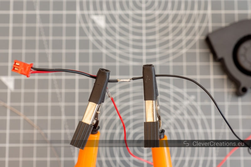Two copper wires with black insulation held in a third hand tool for soldering.