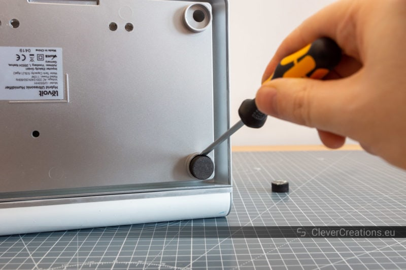 A screwdriver being used to pop out a rubber foot from the underside of an electronic device.
