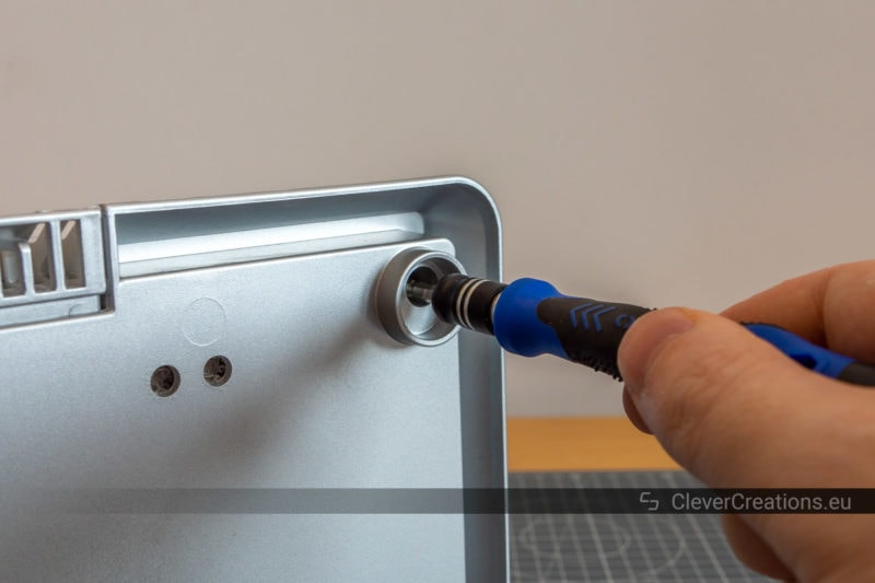 A screwdriver being used to remove a screw to fix a humidifier.