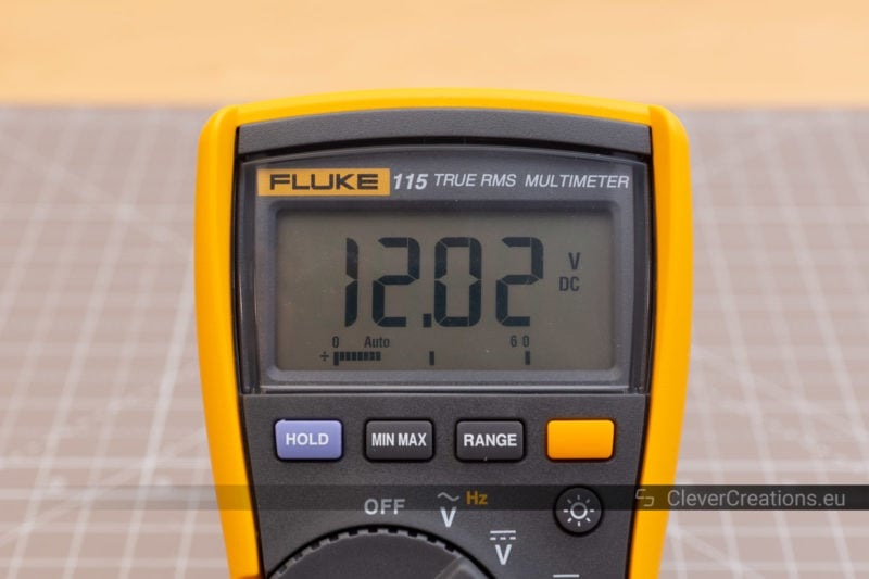 Front view of a DMM measuring 12.02V DC.