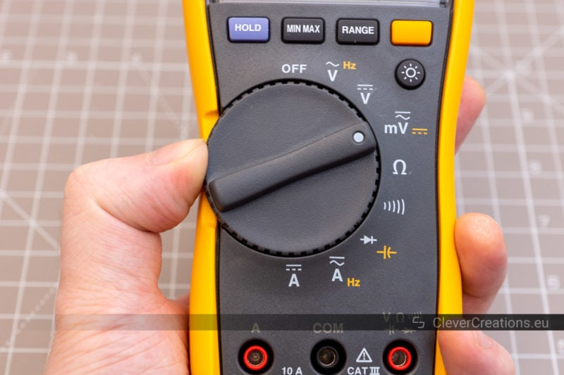 A thumb attempting to adjust the thumbwheel dial of a Fluke 115.