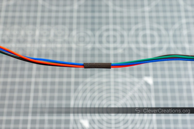 Heat shrink being used to bundle four colored stepper motor wires.