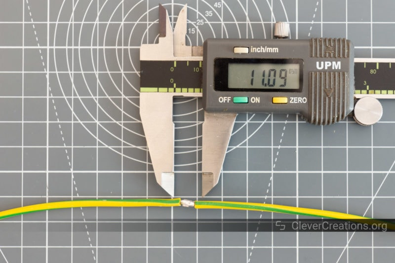 Calipers being used to measure the length of an exposed solder joint on a wire.