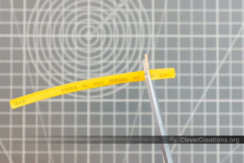 A pair of scissors cutting yellow heat shrink tubing to size.
