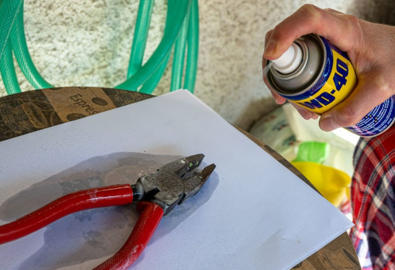 A person spraying WD-40 from a metal can onto a pair of pliers.