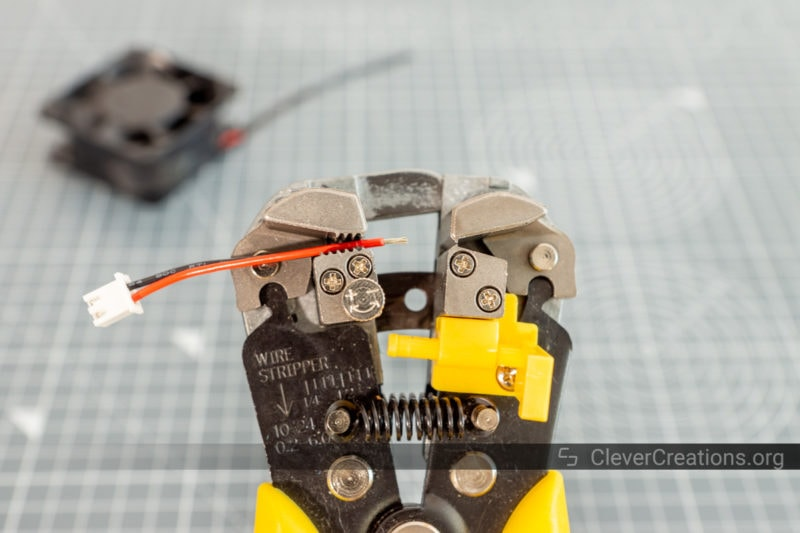 Wire strippers being used to remove the insulation from red and black wires.