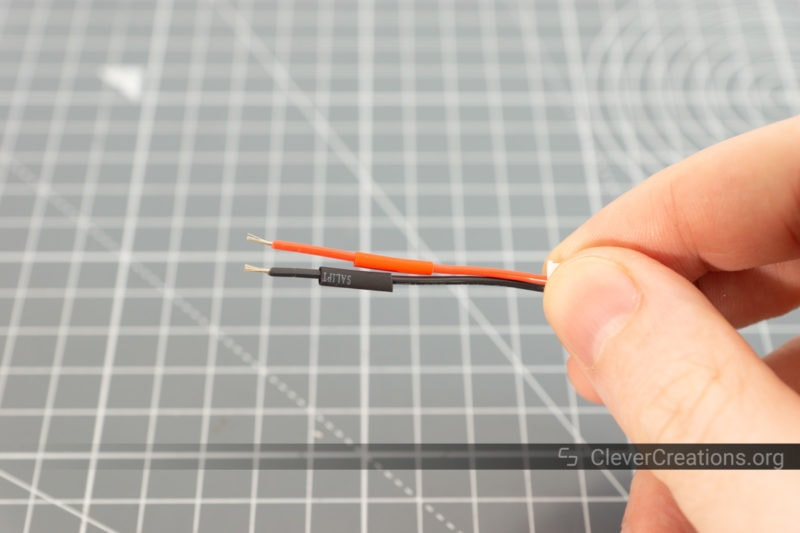 A red and a black piece of heat shrink tubing on wires of matching colors.