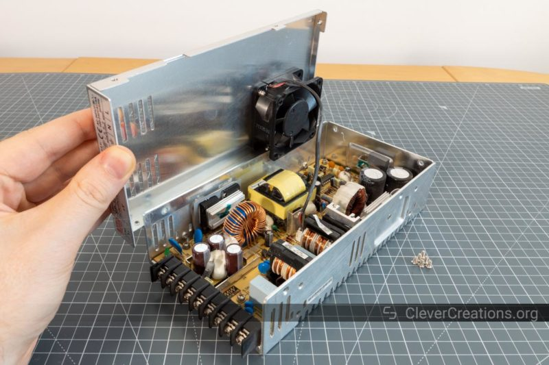 A hand lifting the top cover on a MeanWell power supply.