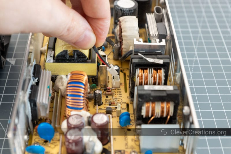 A hand pulling a fan connector from a circuit board.