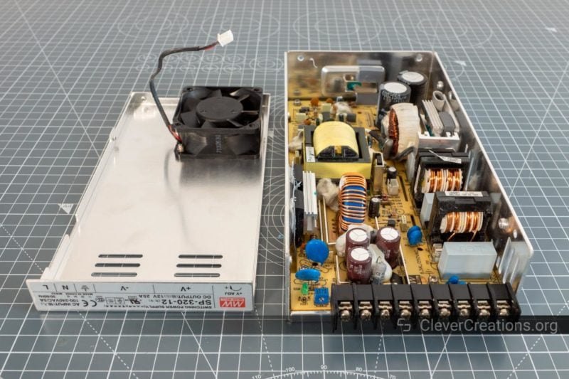 A partially disassembled loud 3D printer power supply with the top cover placed next to the main body.