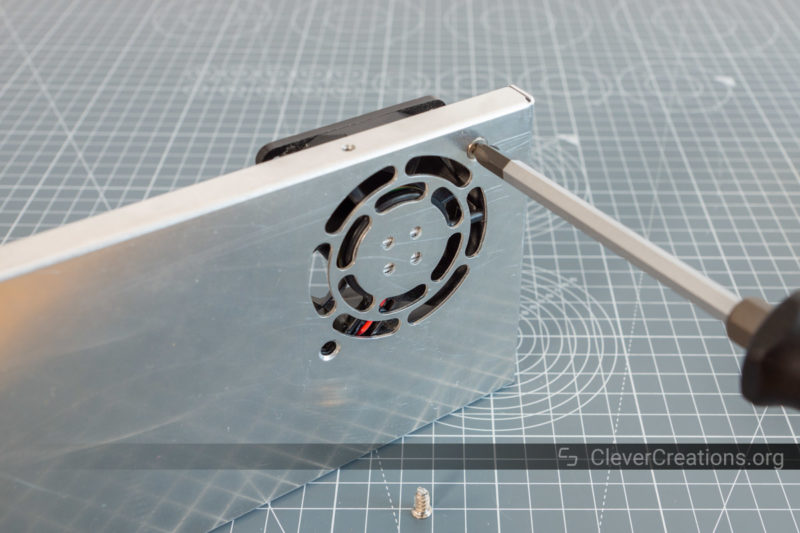 A screwdriver removing a loud 60mm fan from an aluminium lid from a LED PSU.