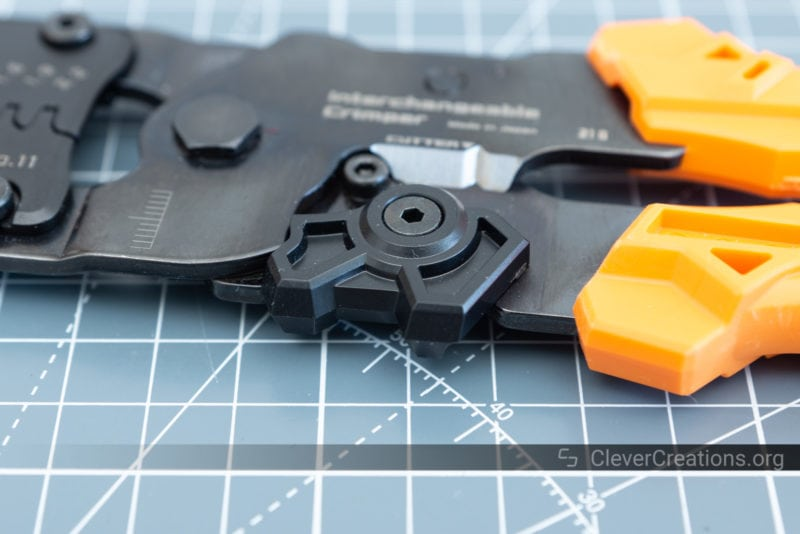 Image with bokeh of the opening/closing latch of the PAD-02 crimping tool.