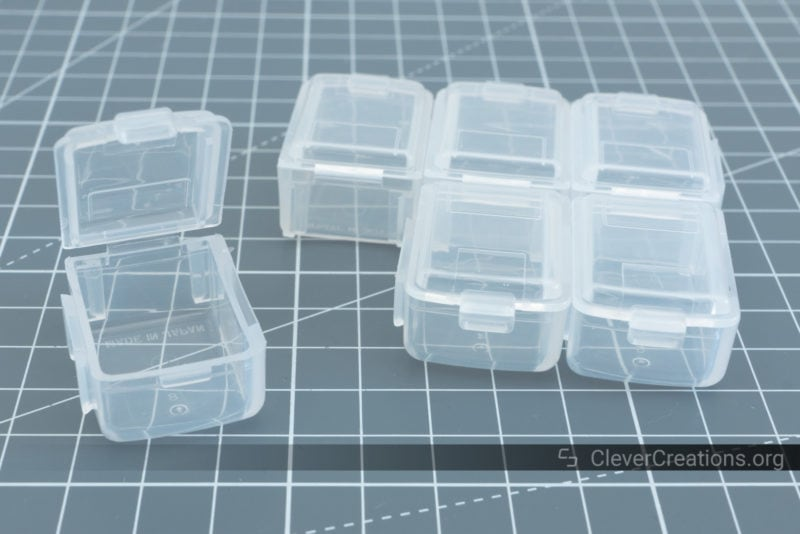 Six transparent plastic boxes for storing small components. Five of them are interlocked. One is placed open on the side.