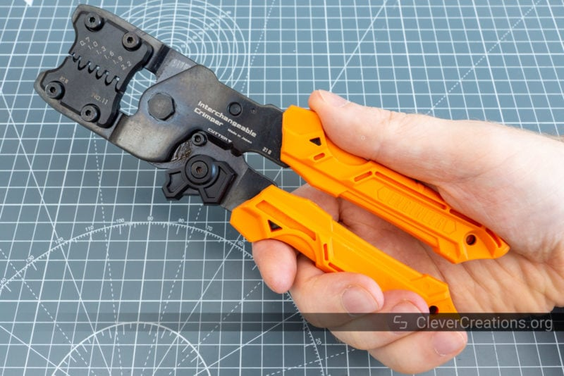 A hand holding a PAD-11 crimping tool correctly.
