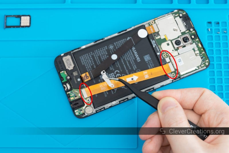 A pair of tweezers holding up a piece of metal shielding in front of a partially disassembled phone.