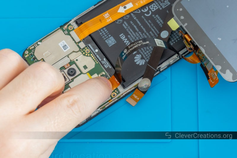 A replacement LCD screen being plugged into a Mate 10 Lite phone.