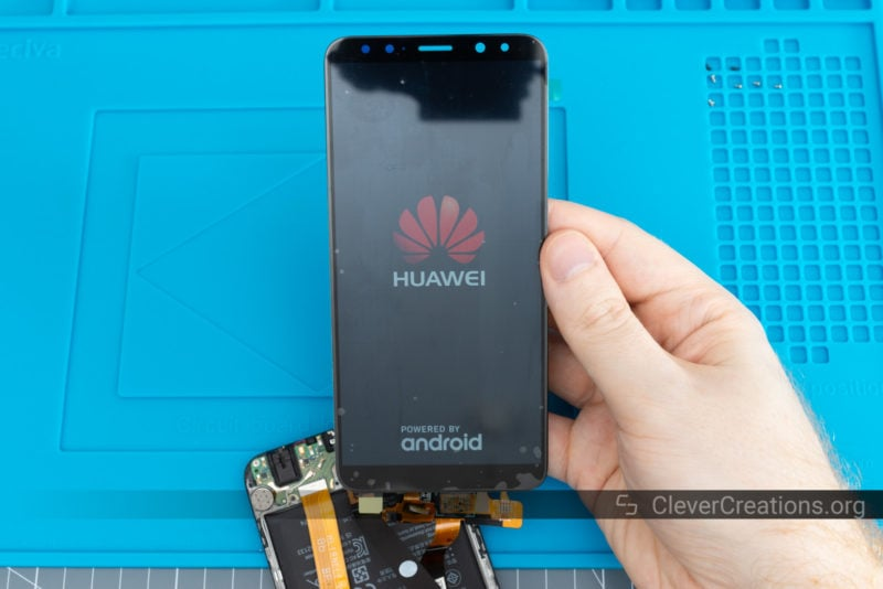 A new phone LCD screen in the process of testing and displaying the Huawei logo and 'Powered by Android'.