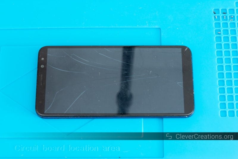 A Mate 10 Lite with a cracked screen lying on top of a blue repair mat.