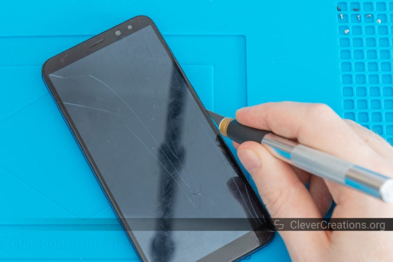 A scalpel separating a LCD screen from the rest of the phone.