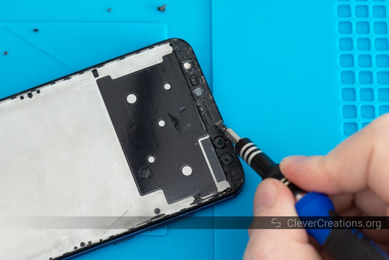 A small flathead screwdriver removing dried phone screen adhesive.