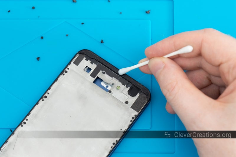 A cotton swab with alcohol used to remove traces of adhesive from a Huawei phone that is being repaired.