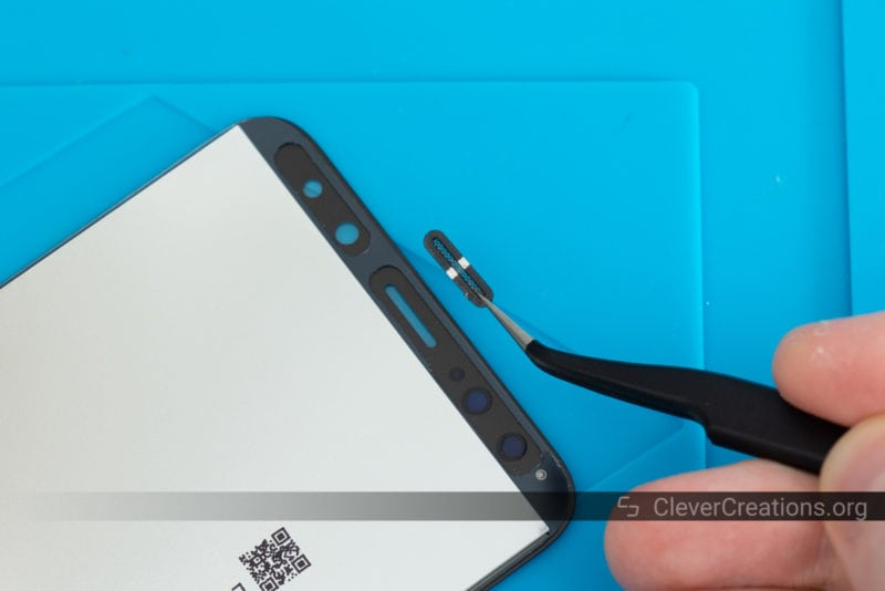 A pair of anti-static tweezers holding a small phone speaker grille up.