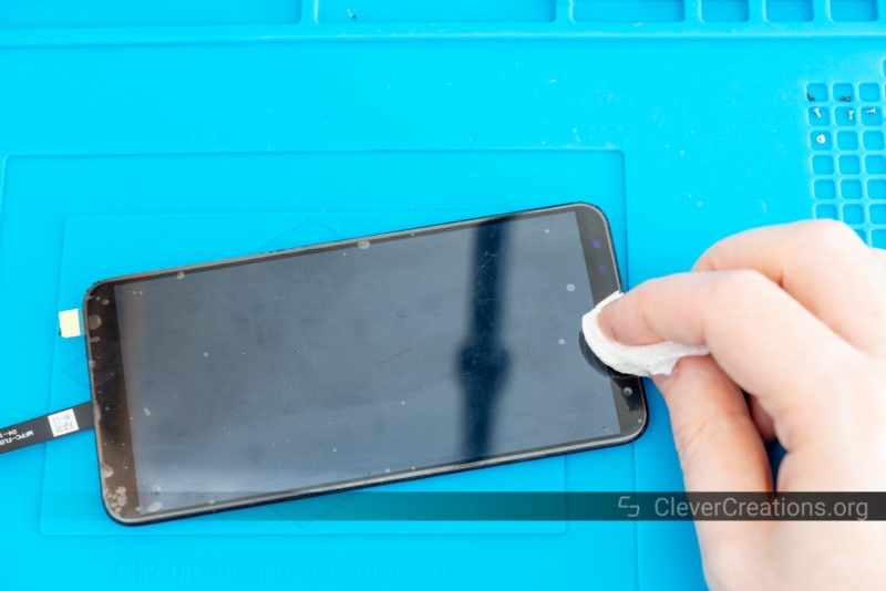 A hand wiping excess T-7000 adhesive from a phone that had its cracked screen fixed.