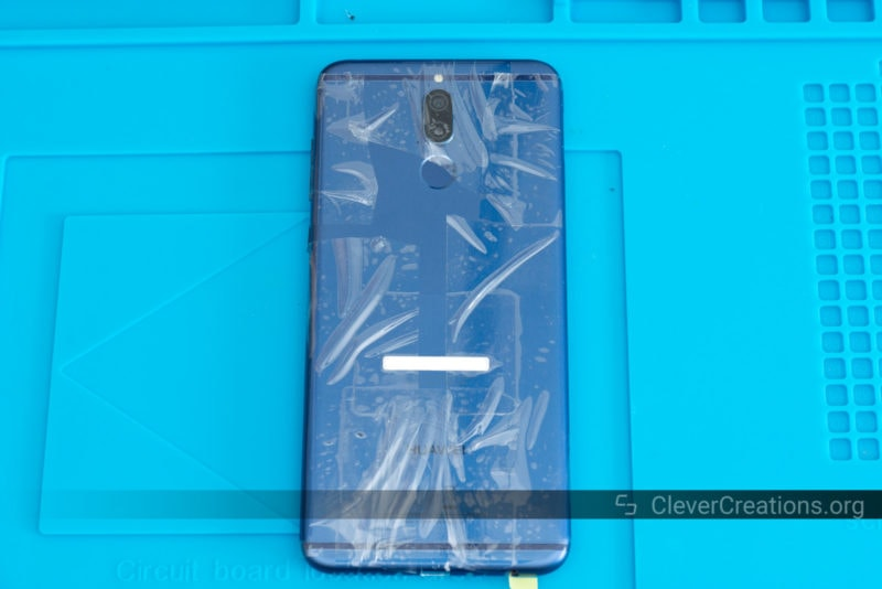 The rear of a phone with sections of clear tape on it.