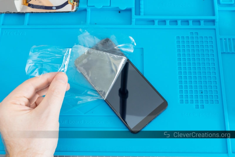 A hand peeling the protective plastic from a phone screen.