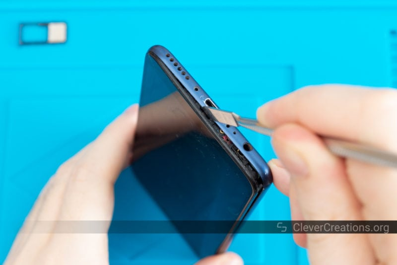 A spudger tool being used to detach the front and back shell halves of a Huawei phone.