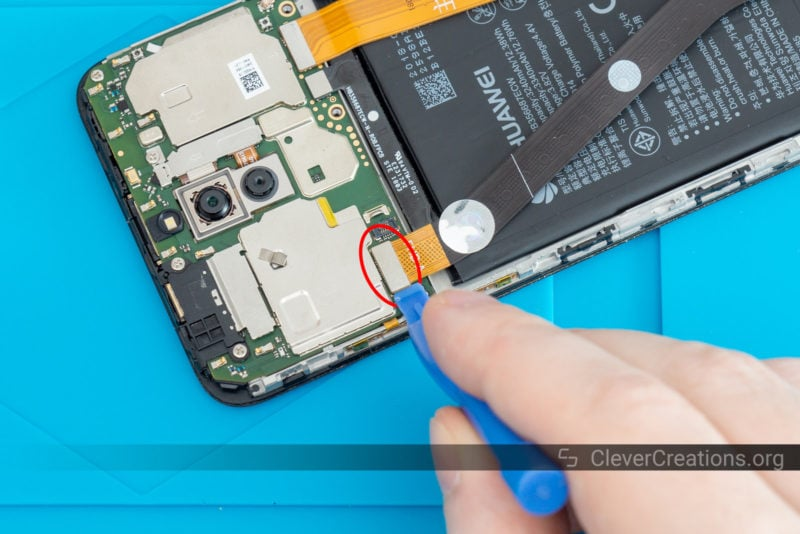 A blue spudger lifting the connector of a flex cable from a phone PCB.