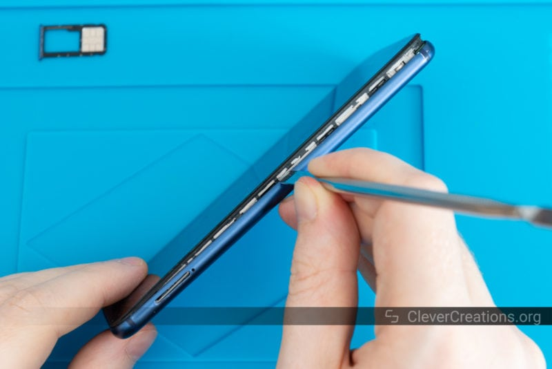 A hand using a prying tool to remove a cracked LCD screen from a Huawei device.