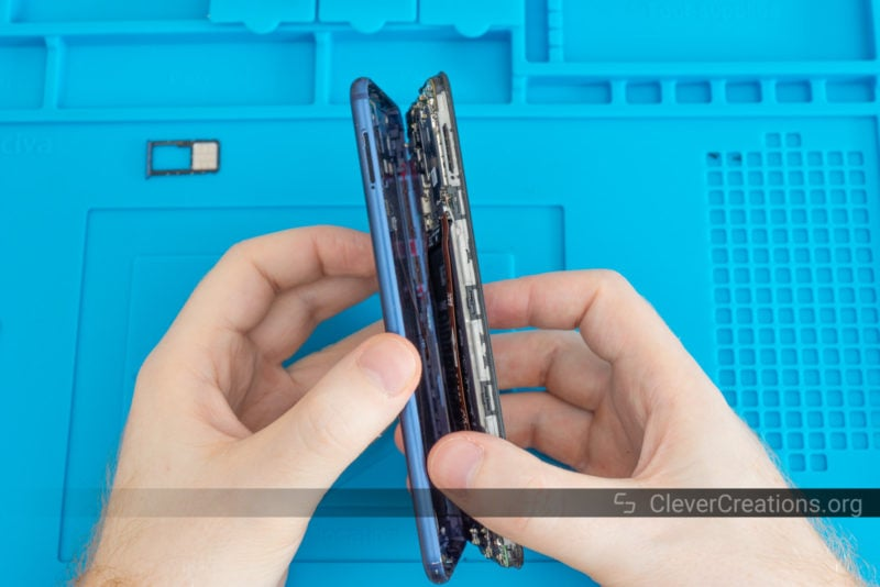 A pair of hands separating the front assembly and back cover of a mobile phone.