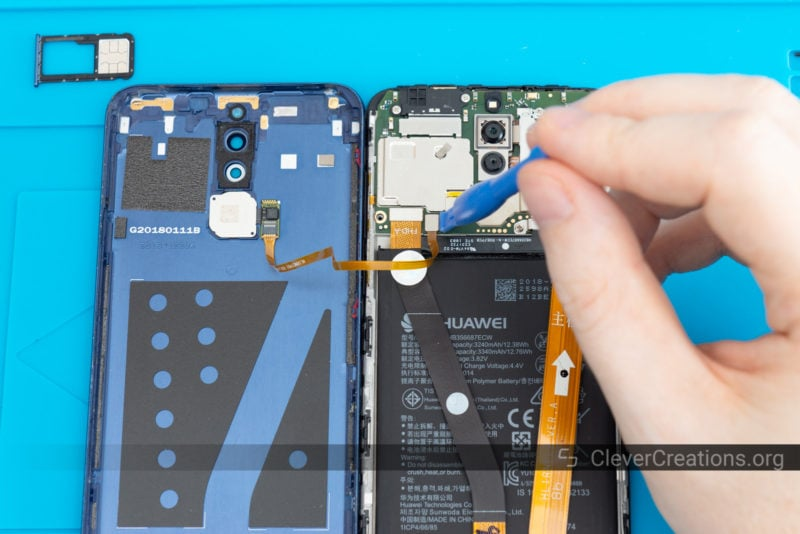 A plastic spudger lifting the flex cable connector from a phone finger print sensor off of a circuit board.