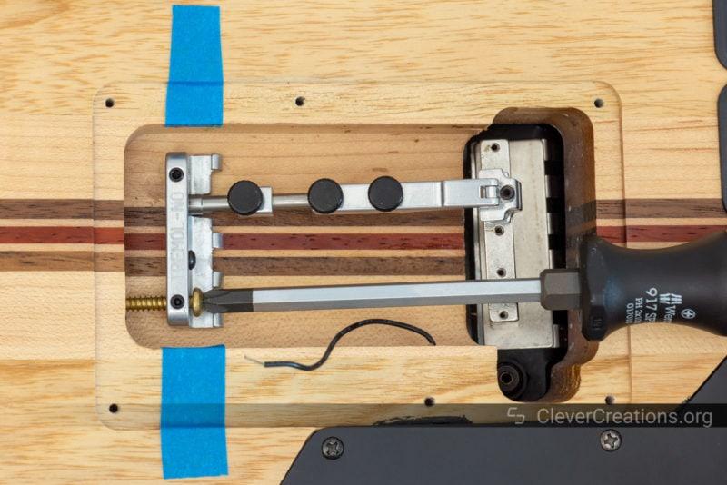 A screwdriver installing the screws of a Tremol-No system into a guitar.