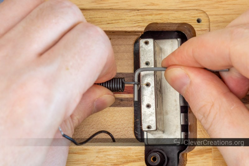 Two hands installing the spring in a Floyd Rose system with the aid of an Allen key.