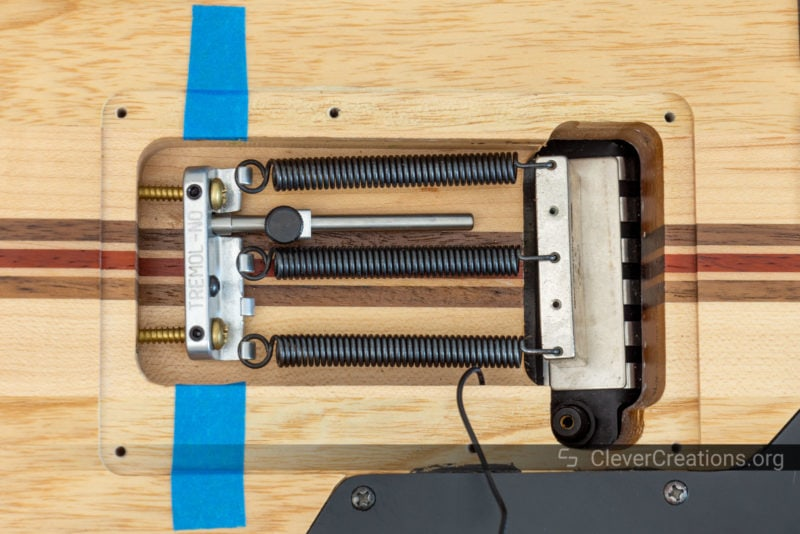 The underside of a guitar that is undergoing maintenance.