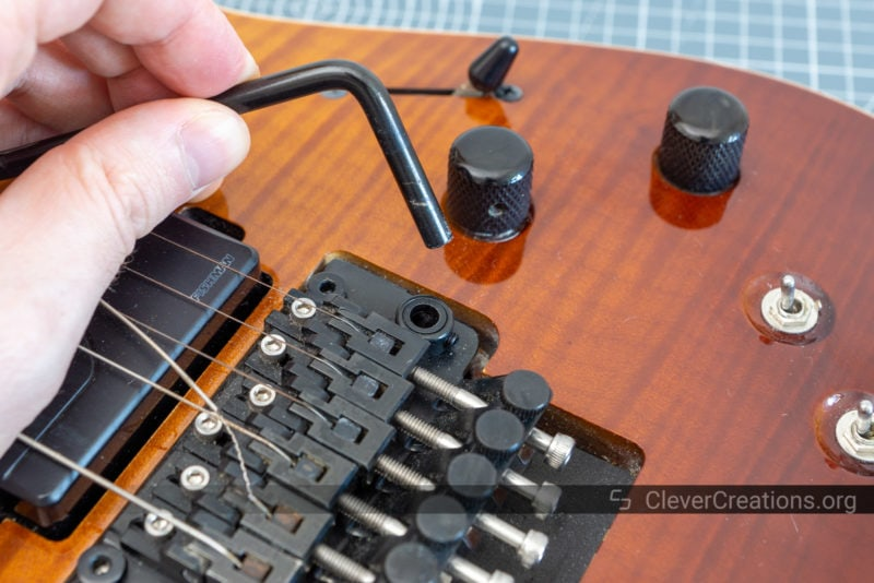 A hand lifting and removing the arm from a Floyd Rose tremolo system