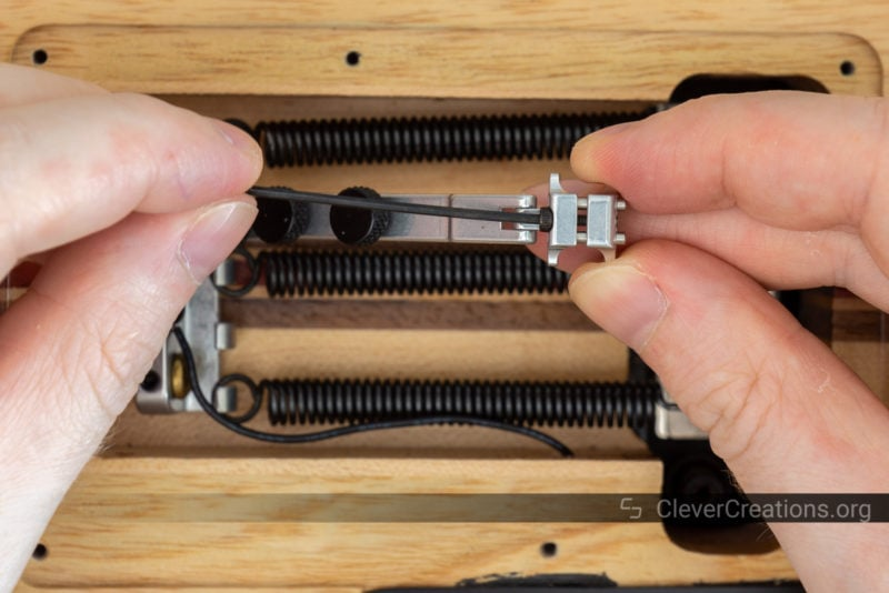 A hand using an Allen key to loosen the retaining bolt of a Tremol-No clamp.